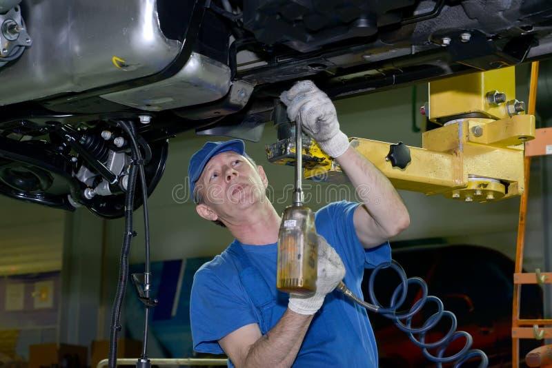 Le travailleur fixe un détail au fond de voiture Chaîne de montage o photographie stock libre de droits