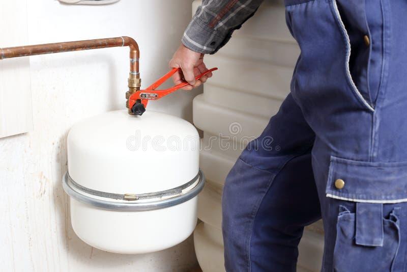 Le travailleur fixe une valve photo stock