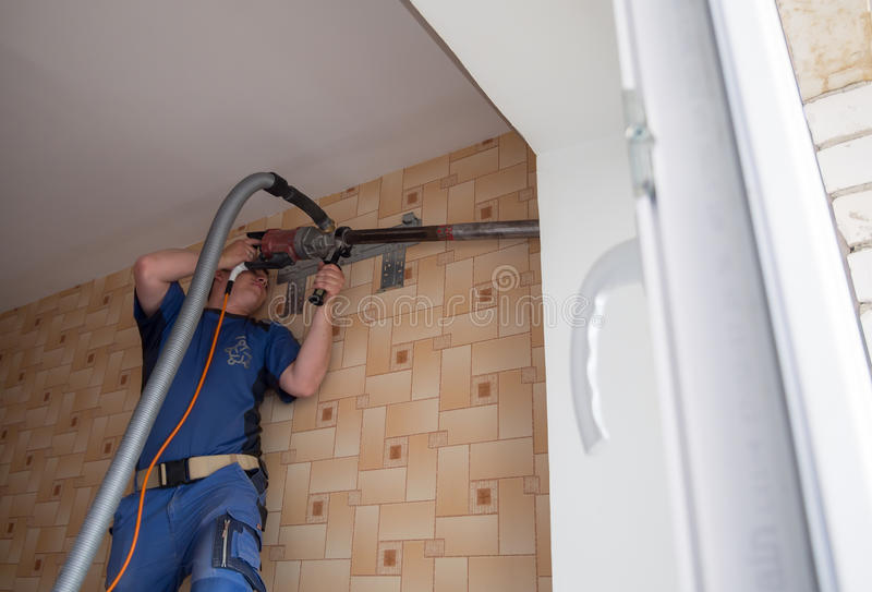 Le travailleur fore le mur avec un perforateur énorme photos stock