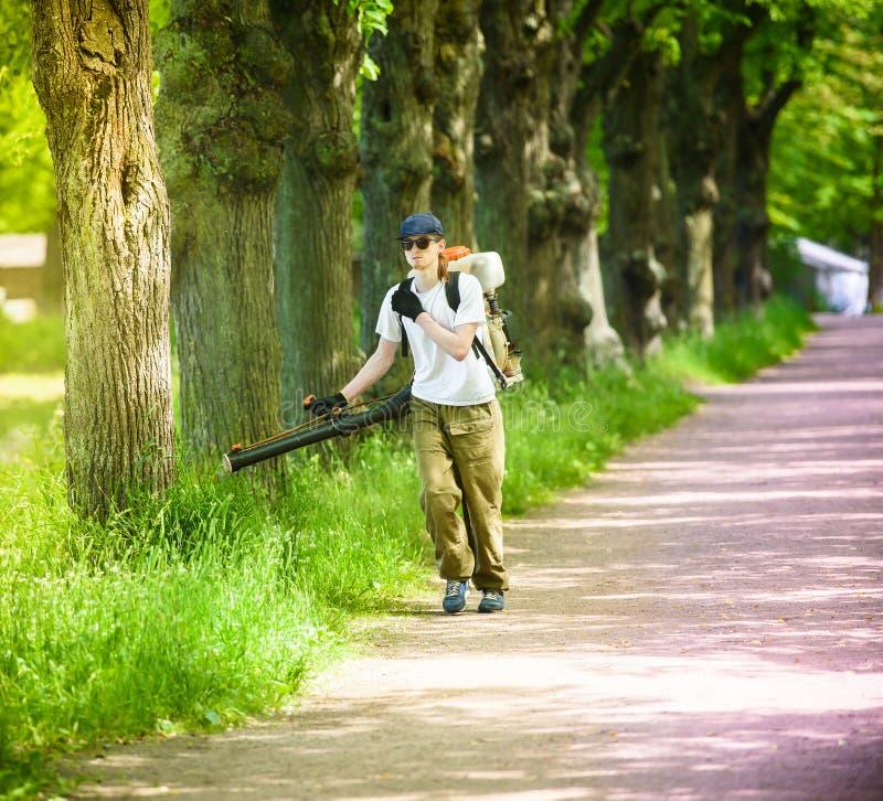 le Travailleur-homme traite un parc contre des acarides et des parasites de récolte photographie stock libre de droits