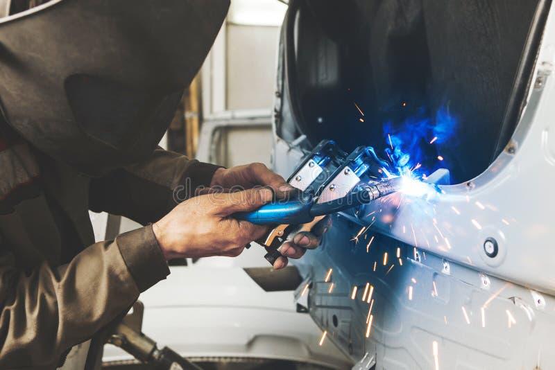 Le travailleur industriel au service de voiture soude la carrosserie de véhicule à moteur Travail des métaux avec la soudure de d photos stock