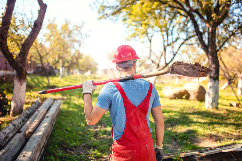 Le travailleur industriel avec le casque et le travail portent utilisant une pelle pour creuser un tunnel concept d'agriculture a photo stock