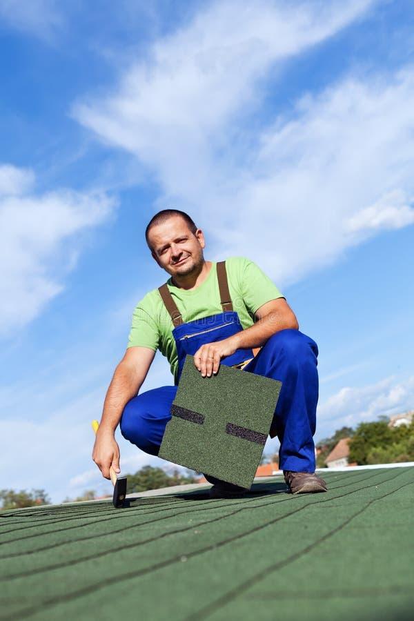 Le travailleur installe des bardeaux de toit de bitume image libre de droits