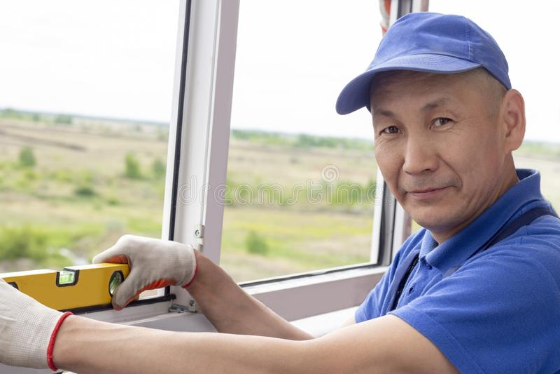 Le travailleur installe des fenêtres que le maître vérifie le niveau de la réparation de cadre dans un bâtiment à plusiers étages image libre de droits
