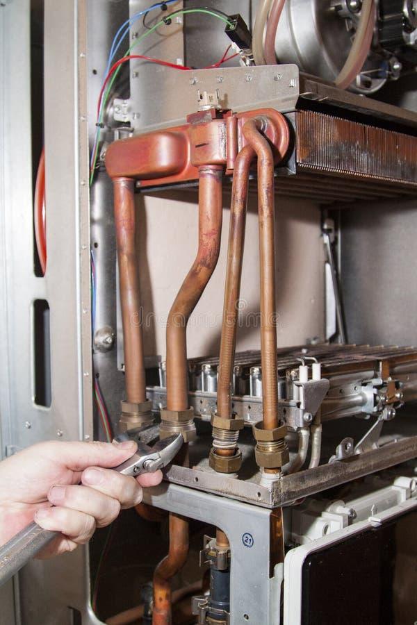 le travailleur installe l'échangeur de chaleur après le détartrage sur un workplac photographie stock