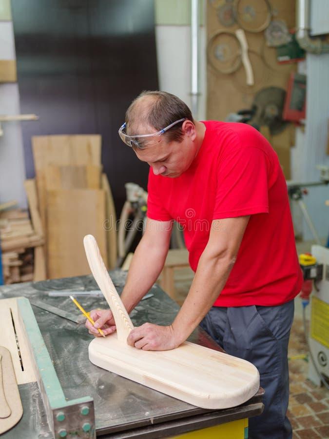 Le travailleur marque les dimensions sur son produit photo libre de droits