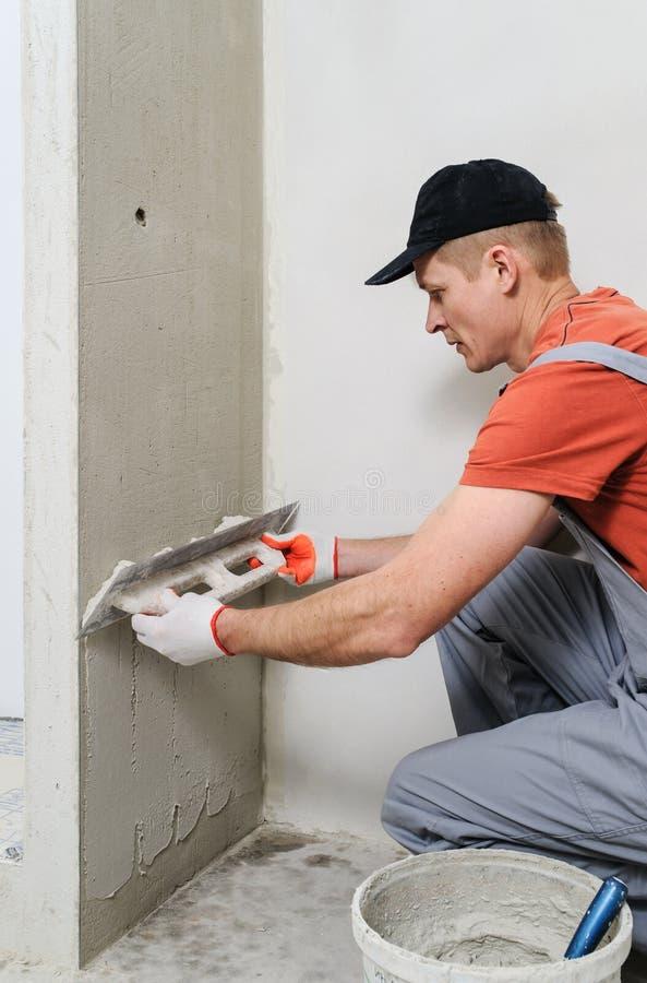 Le travailleur met le stuc sur le mur photos stock