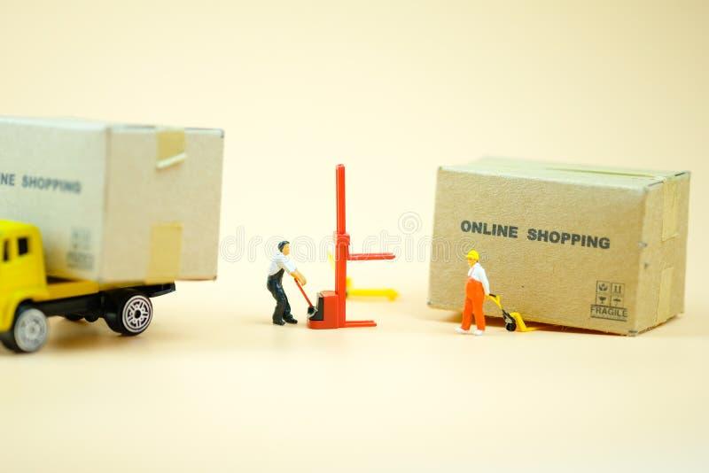Le travailleur miniature d'entrepôt tirant un camion de palette avec les boîtes brunes préparent Concept en ligne d'achats photos stock