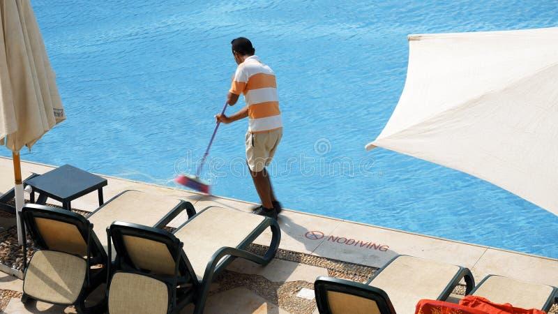Le travailleur nettoie la piscine d'eau avec la brosse images stock