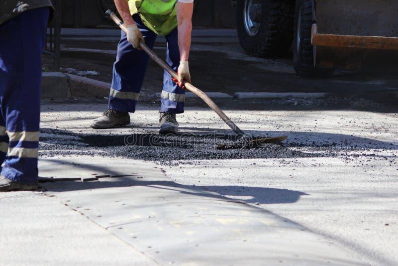 Le travailleur nivelle la miette d'asphalte dans le puits avec un entrave-rouleau avant le pavage avec un mini rouleau de bâtimen images stock