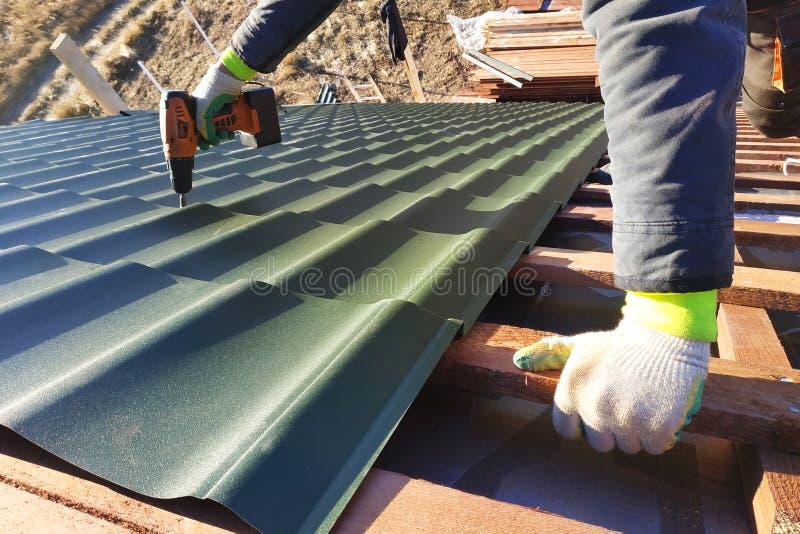 Le travailleur professionnel travaille à l'installation d'un toit d'un toit à côté des feuilles d'une tuile en métal et fore une  photographie stock