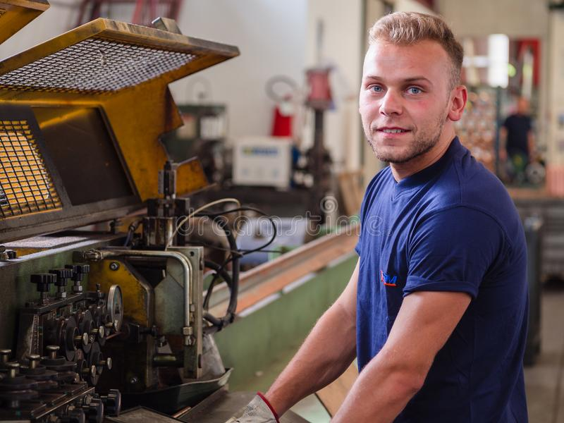 Le travailleur programme la machine de droit-coupe-courbure dans un travail des métaux image stock