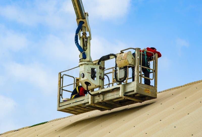 Le travailleur répare la couverture en métal photos stock
