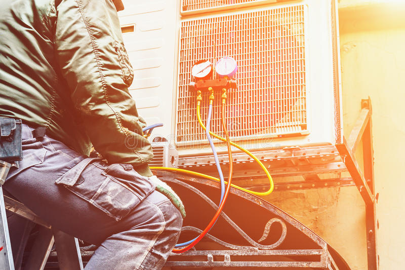 Le travailleur répare ou empêche le climatiseur sur le mur, concept de réparation de climatisation image libre de droits
