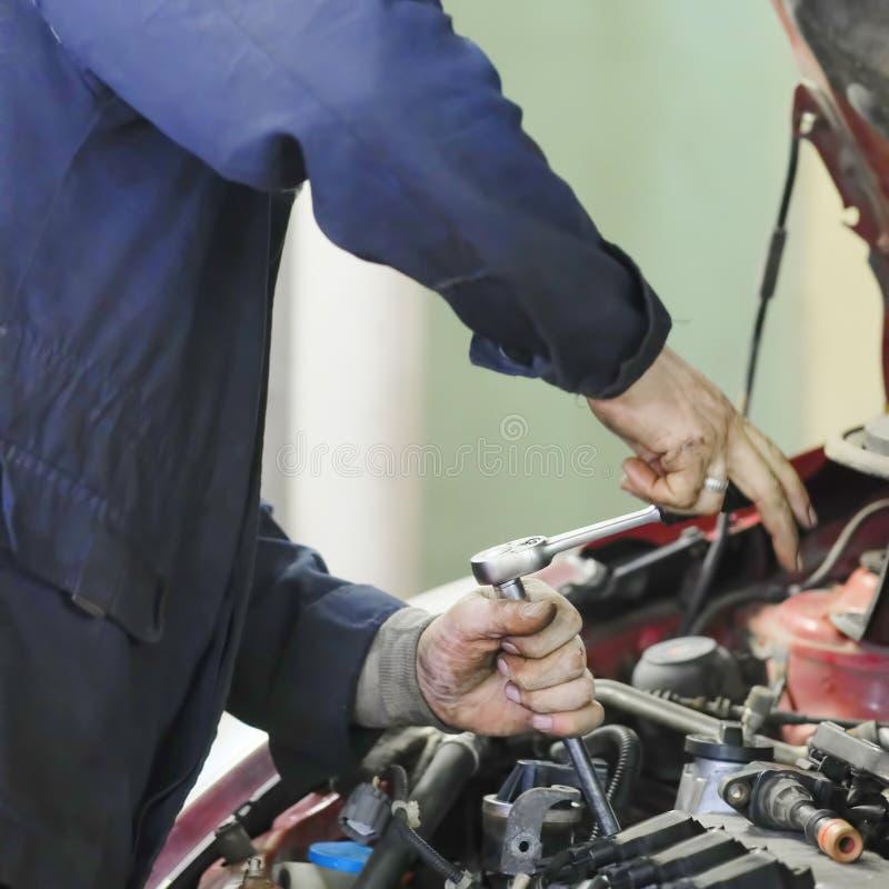 Le travailleur répare une voiture à un centre de réparation de voiture photographie stock libre de droits