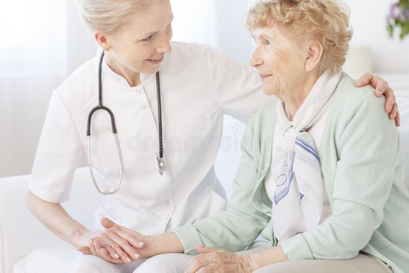 Le travailleur social soulage une dame plus âgée images stock
