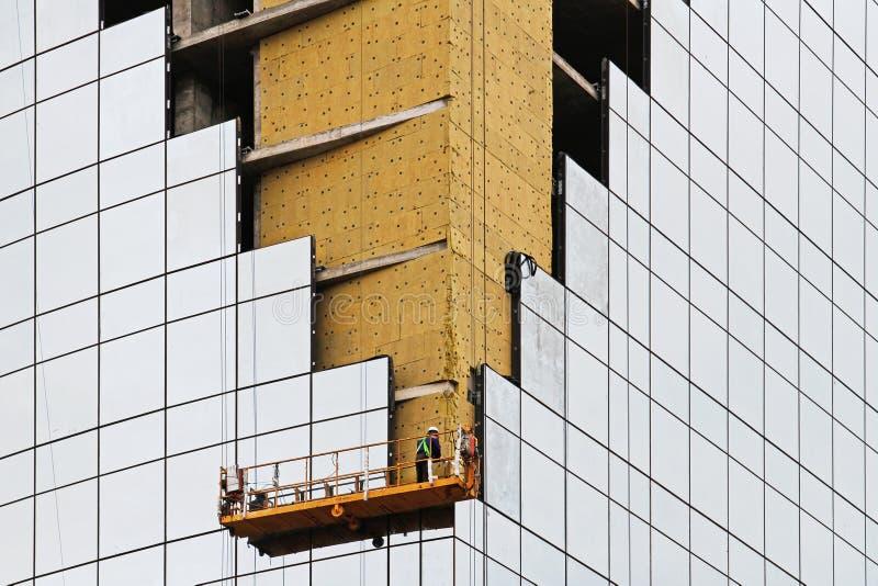 Le travailleur sur l'ascenseur d'échafaudage égalise des panneaux isolants au coin du bâtiment photo stock