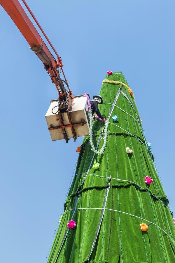 Le travailleur sur la grande grue pendant installent et la décoration ornementent l'arbre de Noël image stock