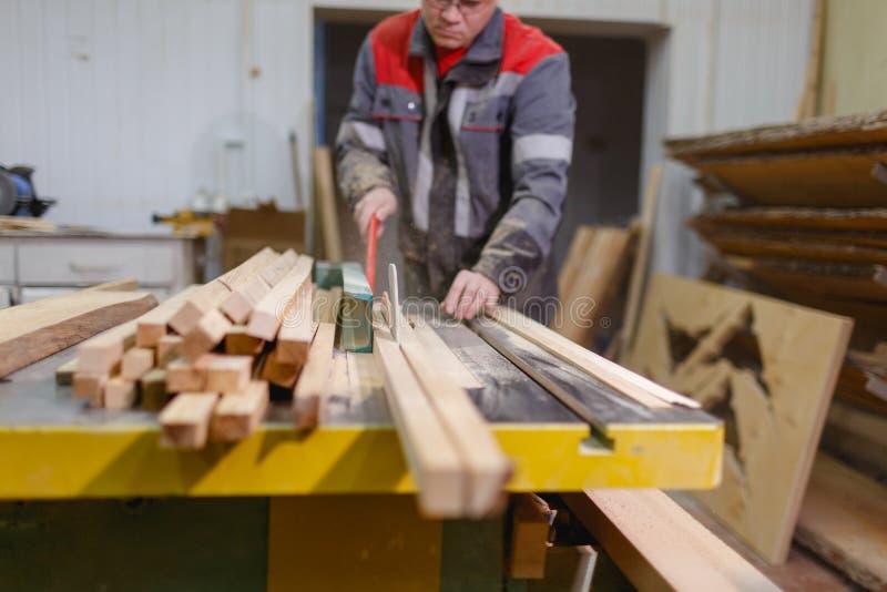 Le travailleur tient un conseil avec un outil spécial sur la mouche de machine et de sciure Front View image libre de droits