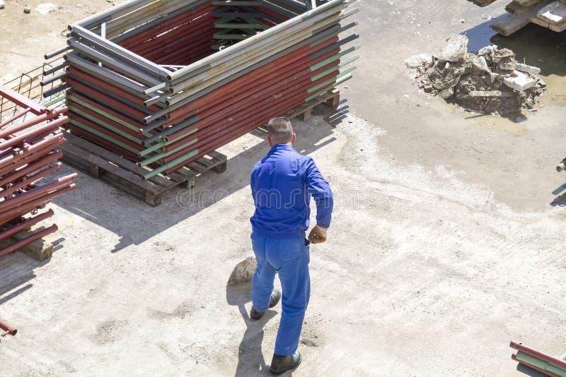 Le travailleur travaille avec une pelle, nettoyant la blocaille photographie stock