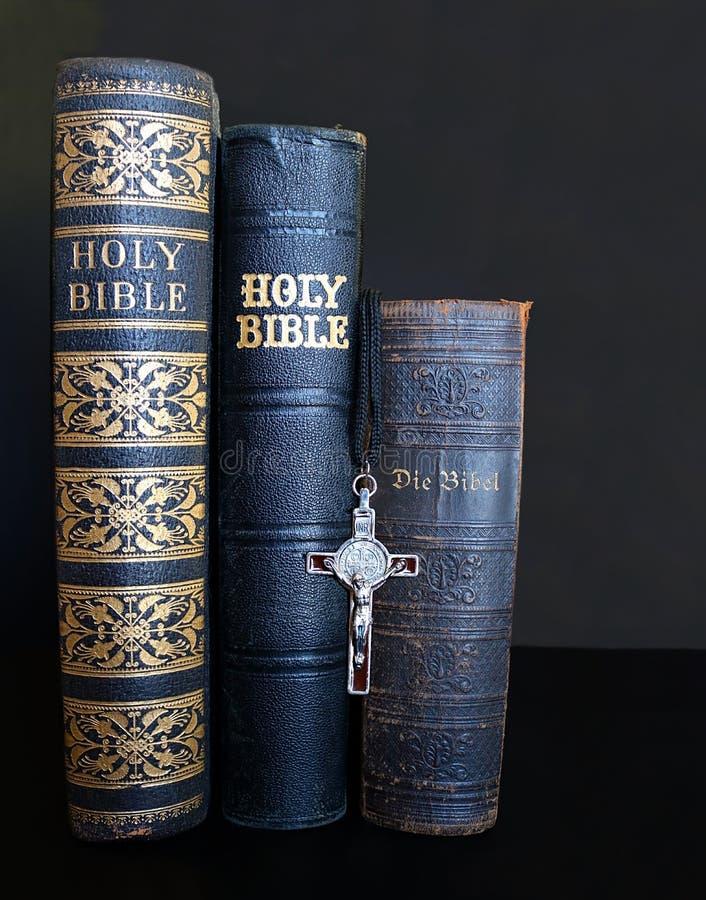 Le tre bibbie antiche con la croce hanno allineato fotografia stock libera da diritti