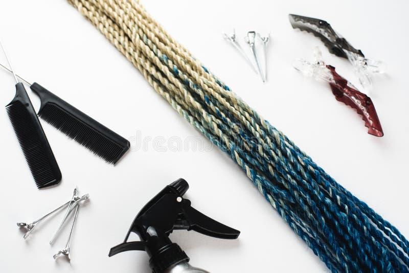 Le trecce artificiali di Senegalese dei capelli di Kanekalon, Ombre colora blu con il pettine e lo spruzzo vicini lattei di clips fotografia stock
