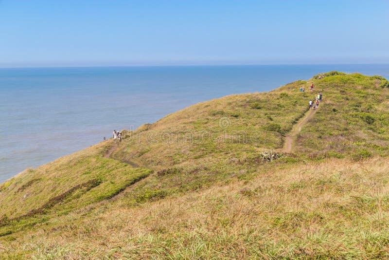 Le trekking au-dessus des falaises et l'océan chez Torres échouent images stock