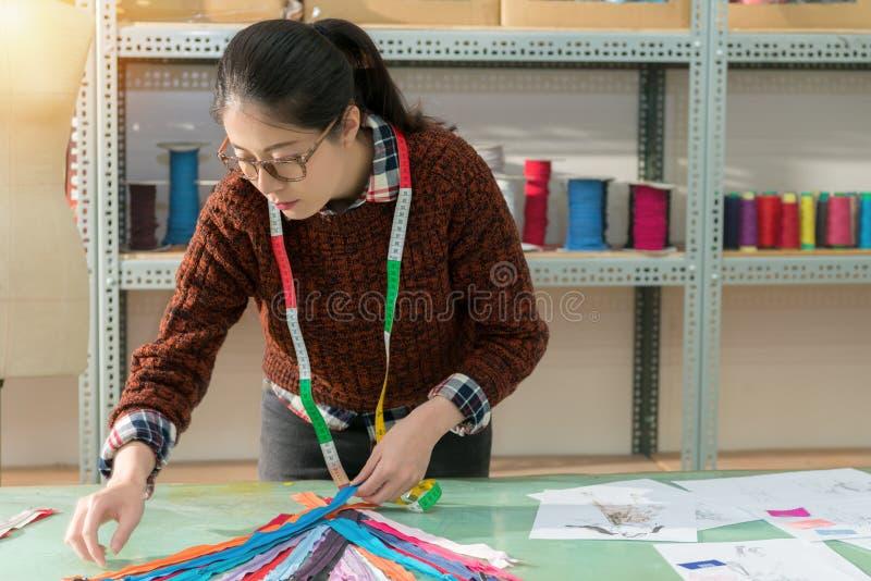 Le trier femelle de fabricant d'habillement beaucoup colorent la tirette photos stock
