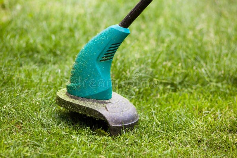 Le trimmer de pelouse d'essence fauche l'herbe verte juteuse sur une pelouse un jour ensoleillé d'été Équipement de jardin photographie stock
