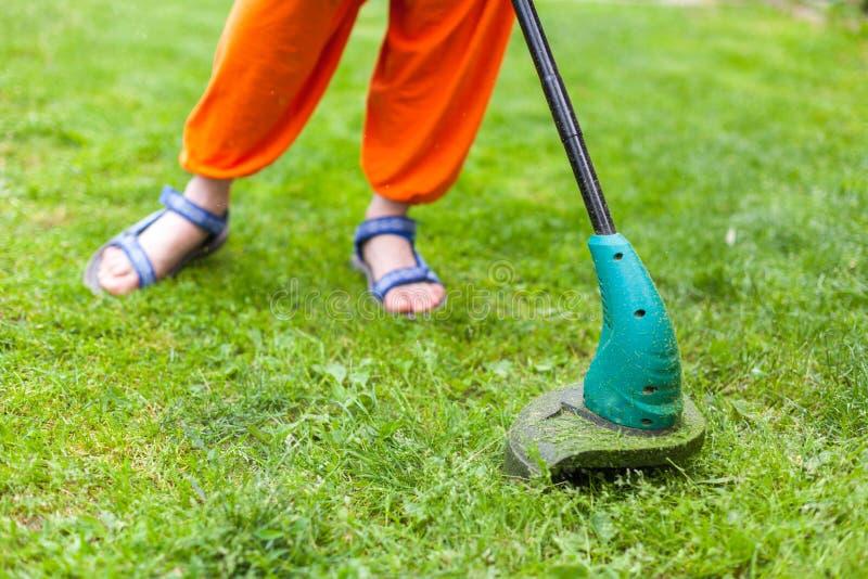 Le trimmer de pelouse d'essence fauche l'herbe verte juteuse sur une pelouse un jour ensoleillé d'été Image en gros plan de foyer images libres de droits