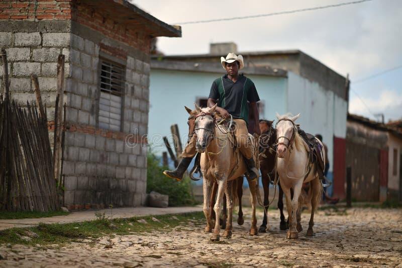 Le Trinidad, Cuba, le 16 août 2018 : Cheval d'équitation d'homme sur les rues du Trinidad photos libres de droits