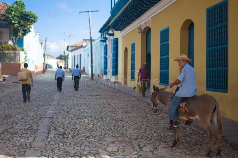LE TRINIDAD, CUBA - 9 NOVEMBRE 2012 : Vieil homme dans le chapeau montant un âne sur la rue photos stock
