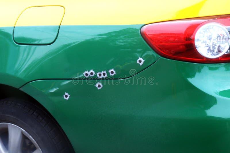 Le trou de balles de marques sur le capot de voiture, trou fendu tiré par balle de shrapnel sur la surface de voiture, tirent la  photographie stock