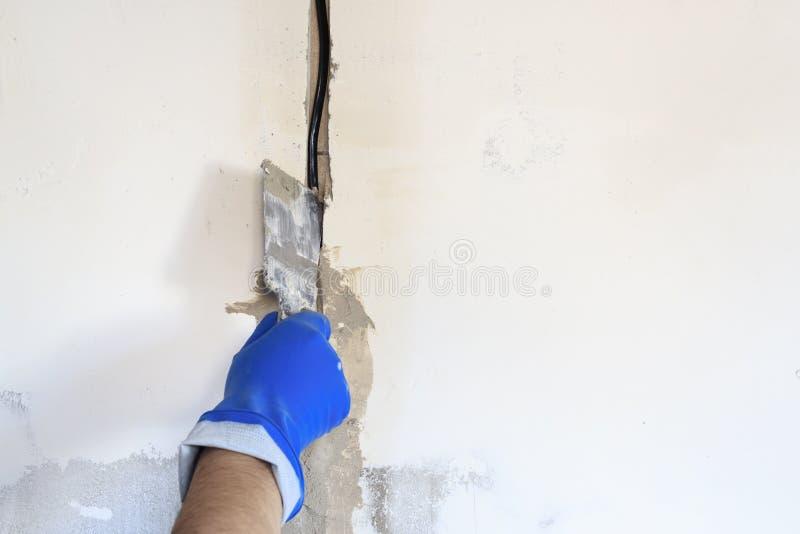 le trou technique dans lui est un fil électrique Le mur est blanc Le maître avec une spatule et un mortier couvre le câble photographie stock libre de droits
