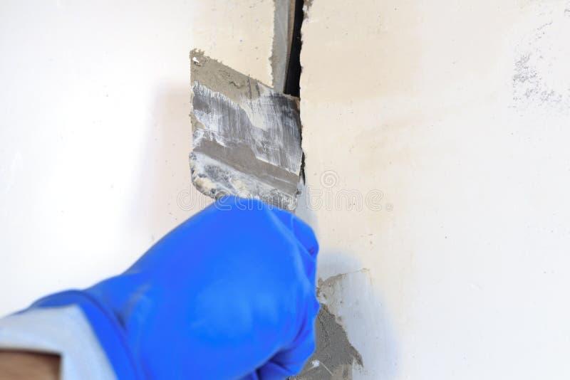 le trou technique dans lui est un fil électrique Le mur est blanc Le maître avec une spatule et un mortier couvre le câble photo stock