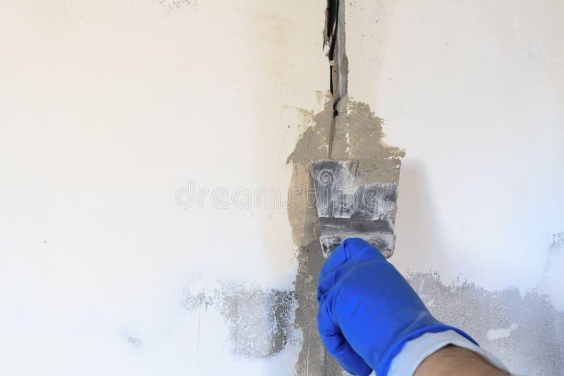 le trou technique dans lui est un fil électrique Le mur est blanc Le maître avec une spatule et un mortier couvre le câble photographie stock