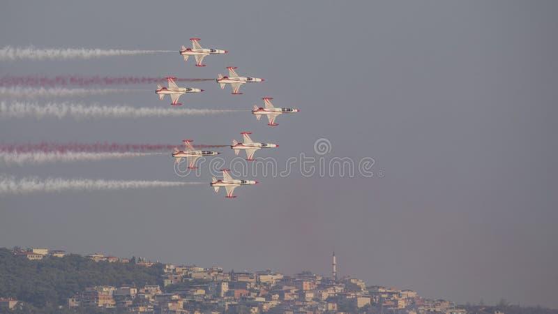 Le turc tient le premier rôle l'équipe acrobatique aérienne dans la formation de 7 avions volant au-dessus de la ville photographie stock libre de droits