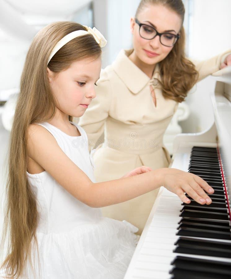 Le tuteur enseigne le petit pianiste à jouer le piano photographie stock