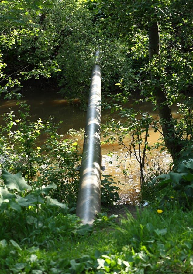 Le tuyau de communication en métal s'est étendu par une petite rivière photo stock