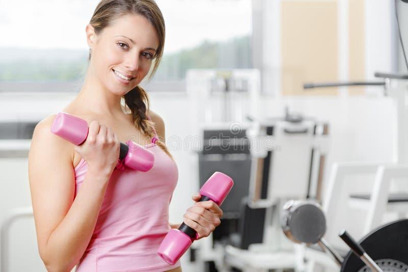 Le tyngdlyftning för ung kvinna på idrottshallen royaltyfri fotografi