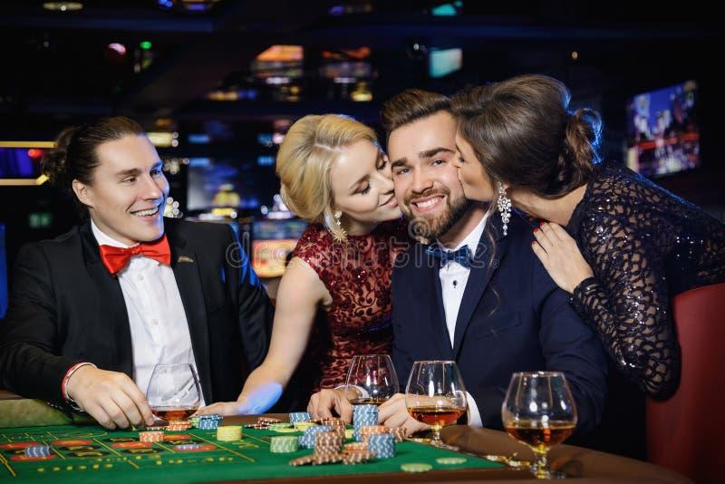 Le type a été embrassé par deux belles filles après victoire dans la roulette image stock