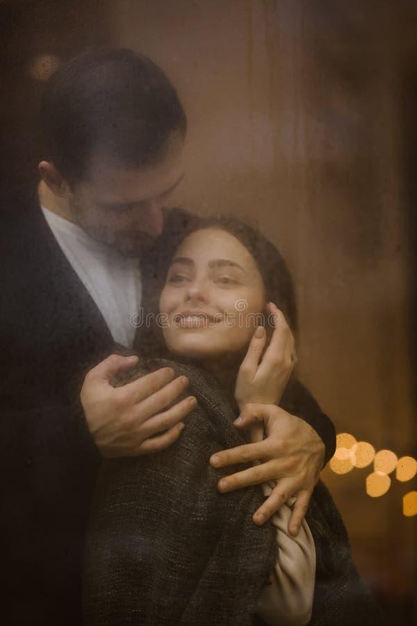 Le type affectueux heureux étreint sa position d'amie derrière une fenêtre humide avec des lumières images libres de droits