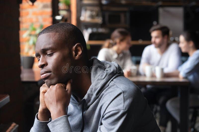 Le type africain triste sentent seule la séance isolée en café photos stock