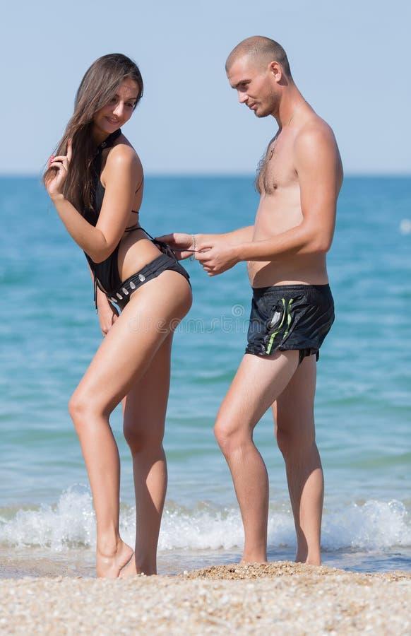 Le type aide la fille à attacher des courroies de son maillot de bain photographie stock libre de droits