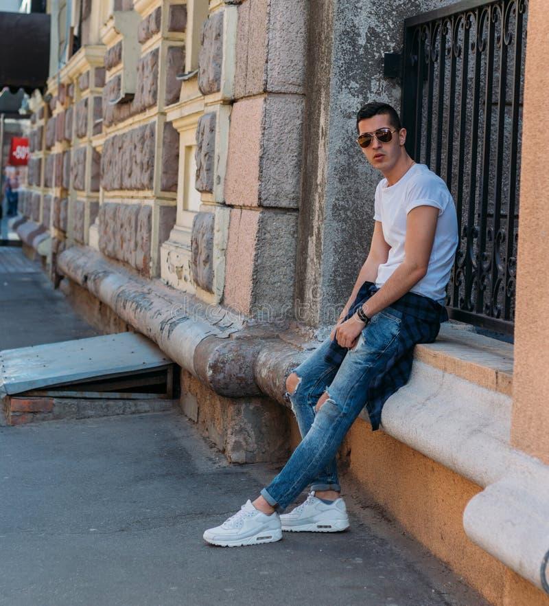 Le type attirant et sexy s'assied sur la rue dans des lunettes de soleil confiance en soi, flatulence et arrogance mod?le, posant photos libres de droits