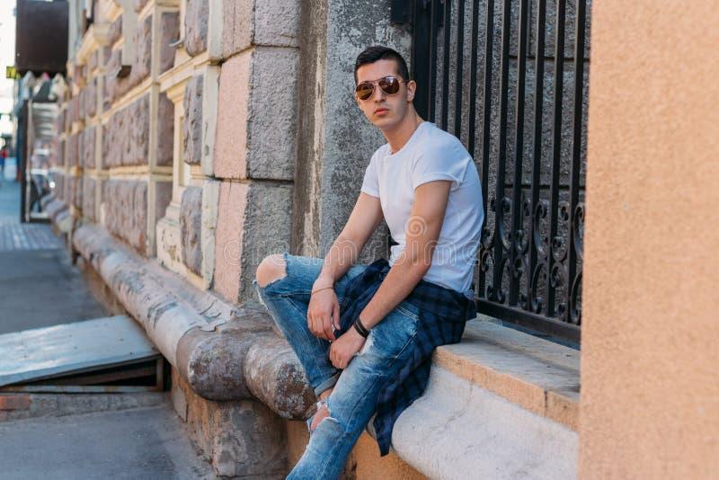 Le type attirant et sexy s'assied sur la rue dans des lunettes de soleil confiance en soi, flatulence et arrogance mod?le, posant images libres de droits