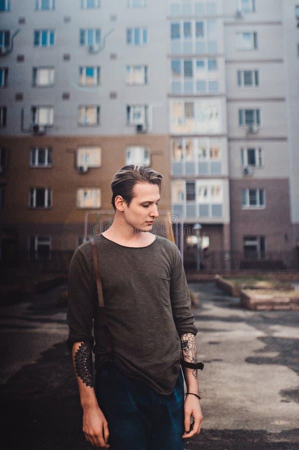 Le type avec des tatouages fume des cigarettes sur la rue, marche dans la ville sur la rue parmi les gratte-ciel images stock