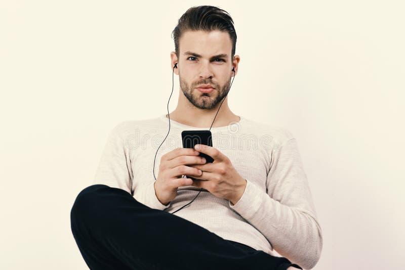 Le type avec la barbe tient le lecteur MP3 et utilise des écouteurs sur le fond blanc Le macho avec les écouteurs et le téléphone images stock