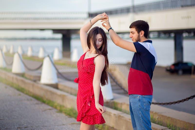 Le type avec la fille de la danse caucasienne de nationalité sur le remblai d'été de la ville photographie stock
