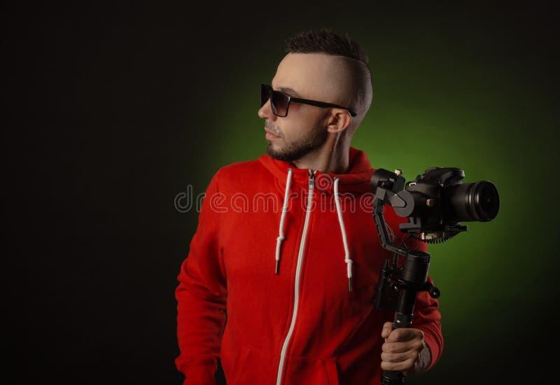 Le type avec le stabilisateur et une caméra de dslr tire la vidéo image stock